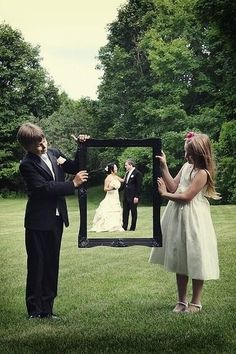 Have your flower girl and ring bearer hold up a decorative frame, ask your photographer position you so that you're within the frame, and snap away!