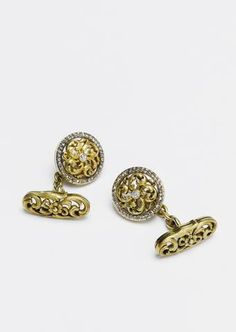 A pair of Fabergé jewelled gold cufflinks, workmaster August Holmstrom, St. Petersburg, circa 1890, each circular disk with scrolling foliate openwork enhanced by central diamond and rose-cut band, chain linked to oval bar of similar design.