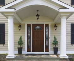 Contrasting colors create a focal point for front door, complete with decorative glass and sidelights. Visit Pella.com