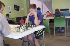 Chess Club! Attention all you chess lovers! The library hosts a Chess Club every Monday from 4:30pm to 6pm and all ages and skill levels are invited to attend. However, young chess players must be accompanied by an adult. BYOCS (Bring Your Own Chess Set) and good luck!   This picture shows a young chess club member in concentration.