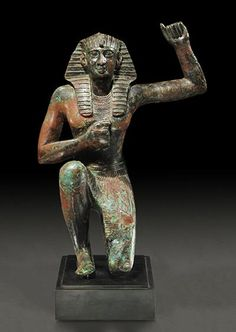 Sculpture from the 26th dynasty 664 - 525 BCE. The last indigenous African dynasty... Kamite King (ancient Egyptian) in bronze kneeling. Wearing the nemes, an usekh necklace and the shendyt kilt; he is holding the right hand on his chest and the left forearm in upright position. The attitude is the 'Henu' pose, a traditional gesture expressing happiness and triumph.