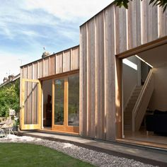 This extension to a north London home comprises three shed-like blocks clad in unfinished larch. British architect Neil Dusheiko designed the single-storey structure for clients who wanted to add an extra living room and bedroom onto the rear of their house. Oak-framed doors fold away from the rear timber wall to open both rooms out to