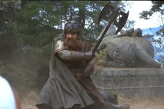 Gimli, Son of Glóin (John Rhys-Davies) swings his battle axe in The Lord of the Rings: The Fellowship of the Ring (2001 New Line Productions)
