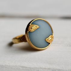 This lovely ring is made from a vintage button from the fifties. Its made of vintage lucite and features an intricate scroll or paisley pattern on a delicate powder blue. The ring focal measures 18mm across and there is a photo of a very similar ring of the same size being worn in the final image, for scale. The ring band is gold plated and is adjustable, so should fit anyone. Any questions, just ask.
