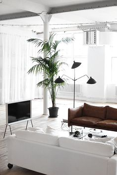 industrial style loft with modern living room furniture | midcentury style floor lamp | tan leather sofa | white sofa | huge palm fronds | Nail the all white trend with a white Bemz cover for your IKEA sofa