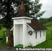 """Sultan, Washington: The Wayside Chapel. """"Pause... Rest... and Worship"""" encourages the sign in front of the always-open Wayside Chapel. Wayside Chapel is approximately 7 ft. x 9 ft. -- just room inside for four small, two-person pews, a pulpit, and two vases of artificial flowers."""