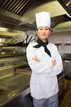Portrait of a confident female cook standing in the kitchen ... 20s, Chefs Hat, Looking At Camera, arms crossed, asian, attractive, beautiful, chef, chefs whites, confidence, cook, female, hands folded, hat, indoors, job, kitchen, portrait, pretty, profession, professional, restaurant, serious, standing, staring, stern, uniform, woman, young adult