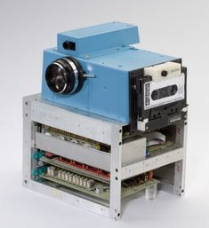 Kodak's first digital camera designed in 1975. It took 23 seconds to record the digitized image to the cassette.  The image was viewed by removing the cassette from the camera and placing it in a custom playback device.  This playback device incorporated a cassette reader and a specially built frame store.  This custom frame store received the data from the tape, interpolated the 100 captured lines to 400 lines, and generated a standard NTSC video signal, which was then sent to a television…