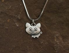 This cute pig necklace is sure to catch peoples attention. Show your love for your pigs with this cute antique silver plated pig necklace -Silver Plated -18 inch snake chain   We get our jewelry from trusted artisans around the globe so some jewelry items can take 2-3 weeks to arrive at your door.