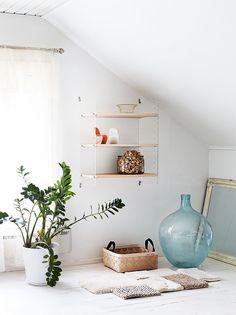 Yläkerran iso makuuhuone on valoisa ja valkoinen. String-pikkuhyllyn päädyt ovat akryylimuovia. Mattokaupan mallipaloista on tehty lattialle sommitelma.