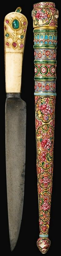 Indian kard (straight dagger), 19th century, watered-steel blade with chiselled palmette near the forte, gold overlay inscriptive cartouche, the gilt steel hilt with marine ivory facings, inlaid in the kundan technique with green and pink gemstones, the scabbard with polychrome enamel decoration featuring floral bouquets within lobed cartouches, with bands of floral scrolls and bud finial, 48.5cm. Dedicated to:Shir Muhammad, the 'Lion of Sindh'.