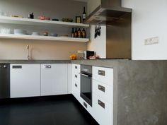 Een mooie, stoere keuken zonder poespas – dat was de opdracht. Daarom: een kloek betonnen aanrechtblad. Geen bovenkasten, maar robuuste planken. Borden, schalen, olie en azijn staan voor het grijpen. In deze keuken wordt gekookt!