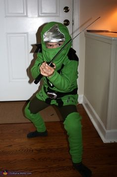 Ginger: My little guy, Drew, loves Lego Ninjago. I made this costume using 2 green long sleeve shirts, black/silver/white fabric, and fabric paint. One shirt was used to make the tunic...
