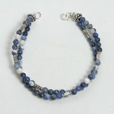 "Handmade gemstone sodalite bracelet features a double strand of semi-precious sodalite round gemstones, sterling silver beads, wire band and lobster claw clasp. 7 1/2"" in length. Add a necklace, penda"