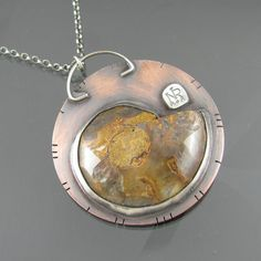This unique necklace features an ammonite, and amber and turquoise gemstones. The ammonite and gemstones are set in sterling silver and the necklace is also sterling silver.    The necklace features my logo stamped on the reverse and was 100% handmade by me.    40mm / 1.6 inch diameter.    The pendant has been given an antique brushed patina, and has been sealed with a thin coating of renaissance wax to protect the finish.    The necklace will arrive in a gift box similar to that picture...