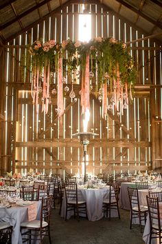 A lush floral and greenery chandelier with pink streamers | @stewartuy | Brides.com