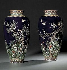 A PAIR OF CLOISONNÉ VASES SIGNED AICHI HAYASHI AND STUDIO MARK, MEIJI PERIOD Worked in various thicknesses of gold and silver wire and coloured cloisonné enamels on a dark blue ground with birds perched and flying among plum blossom, flowers and foliage, the reverse with maple trees, the neck with a band of lappets above a foliate floral design to the shoulder, silver and copper mounts. 24cm high. Christies 2007 - €31,193.