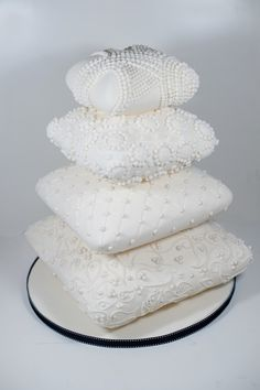 We get the most enquiries about this cake. Stack of pillows cake decorated with a paisley and pearl design.