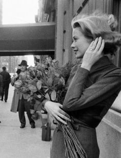 An Engaged Grace Kelly Pose With A Bouquet of Roses.