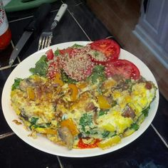 Tomatoes, spinach, hot sauce, garlic, flax seed, peppers, onions, mushrooms, hemp seeds, herbamare, eggs all cooked in coconut oil.