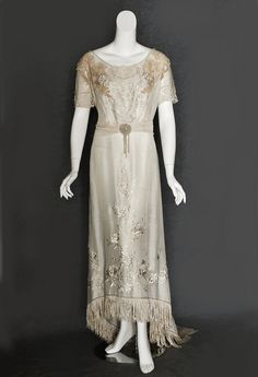 Mixed lace/embroidered silk dress, c.1910..This sumptuous dress combines a nice mix of fine handmade Brussels lace, textured machine made lace, and lovely embroidered roses. Expensive Brussels lace is used on the sleeves and neckline.  The dress was fashioned from pale cream colored silk crepe de chine. The neckline and sleeves were made from matching dotted net and trimmed with Brussels lace. Small pearls outline the neckline and sleeve borders.