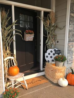 A fall farmhouse look is fun to achieve with just a few pumpkins, corn stalks, and a few welcoming touches. Rustic, autumn front porch! Design by Yellow Prairie Interior Design.