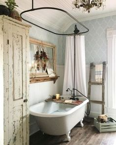 A shabby chic farmhouse bathroom with grey printed wallpaper, a white clawfoot tub, a shabby chic storage unit, a mirror in a wooden frame. House, Country Bathroom, Home, Vintage Bathrooms, Home Remodeling, Shabby Chic Bathroom, Bathroom Interior, Bathrooms Remodel, Beautiful Bathrooms
