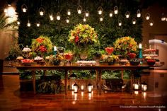 Mais uma vez as velas suspensas me fazendo suspirar. As gaiolas embaixo da mesa com velas no interior remetem a entrega de alianças da cerimônia. Muito verde e flores como decoração e, em vez de madeira, usaria tudo branco.