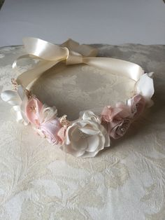 Gorgeous shades of peach pink and ivory handmade roses accented with gold beaded lace pieces on a double side satin ivory ribbon. Ties around the head fits newborns two adults can be used as a sash on babies!