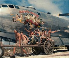 """The crew mimics their caricatures on their B-29 bomber! On Jan. 9, 1945, """"Waddy's Wagon"""" was among 72 B-29s sent to bomb the Nakajima Aircraft Engine Factory near Tokyo. Attacked upon reaching their objective, the aircraft to the immediate right of Young's in the 8-ship formation was rammed by a kamikaze fighter. """"Waddy's Wagon"""" and its 10-member crew were last sighted 10 miles east of Choshi Point off mainland Japan at 27,000 feet and descending into clouds while providing protection to…"""