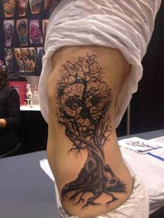Skull in branches and tree tattoo. Side placement.