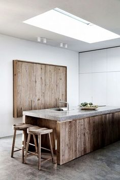 White-washed kitchen with salvaged wood doors, marble countertops, and wood stools