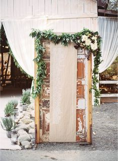 DIY your wedding ceremony table numbers post it on a vintage door. The florals really make everything pop. For more on this wedding, visit The Venue Report.