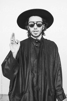 A man wearing black robes making a peace signal with his hand by Stalman & Boniecka #stocksy #realstock