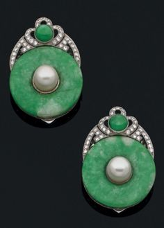 A pair of Art Deco platinum, jade and diamond clips. Each designed as a jade disc, enhanced with a pearl, and surmounted by a diamond and jade-set motif, mounted in platinum. #ArtDeco #clip
