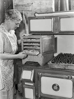 "September 1942. Canfield, Ohio. ""Mrs. Frank Rogers looking at a tray of blanched pencil pod beans on the dryer on top of a coal and wood ran..."