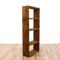 This simple bookshelf is featured in a solid wood with a rustic pine finish. This tall bookcase is in good condition with 3 tier shelves and a sleek, straight design. Perfect for displaying books and knick knacks! #bohemian #storage #bookcase&shelving #sandiegovintage #vintagefurniture