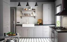 Uma cozinha campestre com portas encastradas cinzentas*, bancada preta e maçanetas e puxadores cromados