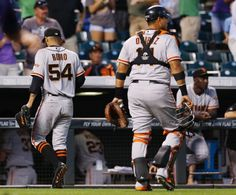 the San Francisco Giants relief pitcher Sergio Romo, left, walks off the diamond with catcher Guillermo Quiroz after Romo gave up a walkoff, RBI-single to Colorado Rockies' Charlie Blackmon in the ninth inning of the Rockies' 10-9 victory in a baseball game in Denver on Monday, Sept. 1, 2014. (AP Photo/David Zalubowski)