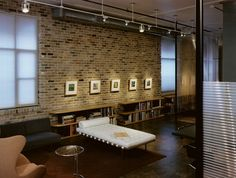 Gorgeous lighting and brick wall create an art gallery-styled display in the Downtown Austin home [Design: Tim Cuppett Architects]
