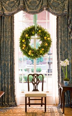 A wreath of evergreen, lemons, limes, and other fruits adorns this entry window at Blair House - Traditional Home®