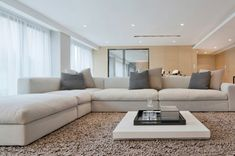 An oversize white linen sectional takes center stage in this open space living/dining space. An unusually low coffee table sits on a deep pile area rug.