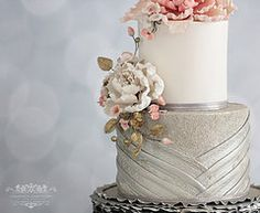 Champagne coloured metallic wedding cake. Royal Melbourne Show Winner 2015. Elegant Wedding Cake.  Rose Ruffles. Pleated fondant. Lace mats, Edible Lace. Gumpaste peony. Sugar paste peony. Champagne textured cake. 3 tiered wedding cake. Silver ruffles. Gold ruffles. Metallic finish. gold Cake. Carasmatic Cake Studio. Cara Schneider
