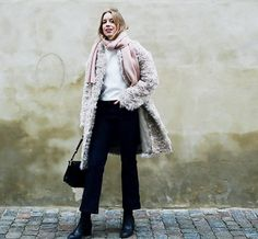 A white top is paired with a fuzzy coat, pink scarf, cropped trousers, and boots