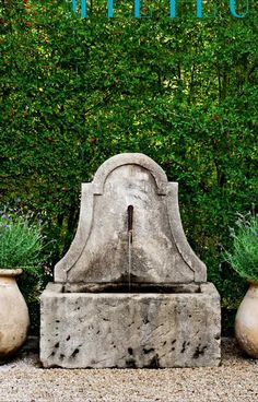 Classic water fountain. Love it flanked with those simple urns.