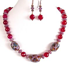 BERRYLAND: 20″ Beaded Jewel Tone Necklace Set. Bold hues of semi-precious berry jade and purple agate complement the intricate lampwork glass focals in this handmade set. $72 https://earthandmoondesign.com/shop/beadz-by-roz/berryland-20-inch-beaded-jewel-tone-necklace-set/