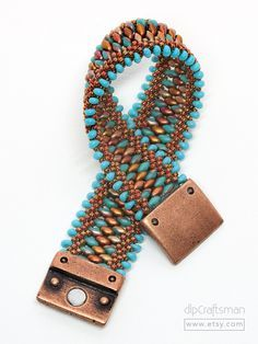 Turquoise & Copper Kumihimo Cuff Bracelet. This eye-catching handmade cuff bracelet is a combination of kumihimo braiding and bead weaving techniques. Turquoise SuperDuo beads in a matte Apollo finish, gilded copper seed beads and turquoise Magatama drop beads were braided together using an intricate pattern in two sections. The two sections were then joined together...bead woven using an additional row of iridized copper SuperDuos. The bracelet is completed with a strong magnetic clasp ...