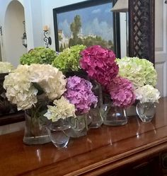 Hydrangeas displayed in different sized and shaped glass vases for a seaside inspired dinner.