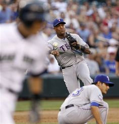 Seattle Mariners' Ichiro Suzuki, left, races to first as Texas Rangers reliever Martin Perez ducks to allow third baseman Adrian Beltre to make the throw for an out in the ninth inning of a baseball game Saturday, July 14, 2012, in Seattle. The Mariners won 7-0. (AP Photo/Elaine Thompson)