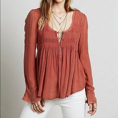 "Free People Blue Bird Smocked Top NWT Free People Blue Bird Smocked Top in the color ""pink sand"", which is a rust/orange color and is beautiful for the season! Size small. Still on the FP website for full price but this size is sold out everywhere. I'm open to offers!  100% rayon  Crochet trim Raw hem Free People Tops Blouses"